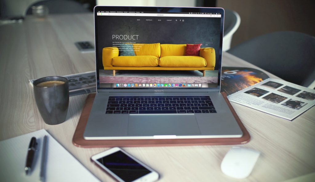 website yellow theme on a laptop on a table with coffee and cellphone on the side
